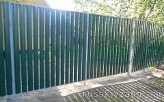 Забор из металлического штакетника темно-зеленого цвета с ровным верхом
