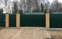 Раздвижные откатные ворота с калиткой из зеленого евроштакетника RAL 6005 с кирпичными столбами.