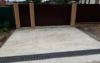 Площадка из бетона при въезде на участок с бетонированием дренажного русла, защищенного декоративной металлической решеткой