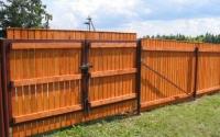 Забор из окрашенного дерева с округлым верхом с воротами на трех лагах