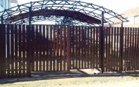 Забор из металлического штакетника коричневого цвета и навес для машины