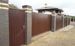 Забор из профлиста с декоративными столбами из кирпича на монолитном фундаменте