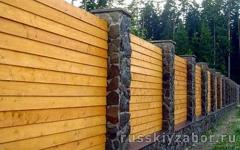 Горизонтальный сплошной деревянный забор на ленточном фундаменте с монолитными столбами, отделанными плитняком