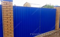 Забор из синего профнастила RAL 5002 на монолитном фундаменте с кирпичными столбами