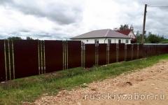 Комбинированный забор из секций профнастила и металлического штакетника с бутированием столбов гравием
