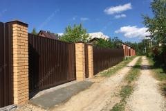 Забор из коричневого профнастила RAL 8017 c кирпичными столбами на ленточном фундаменте